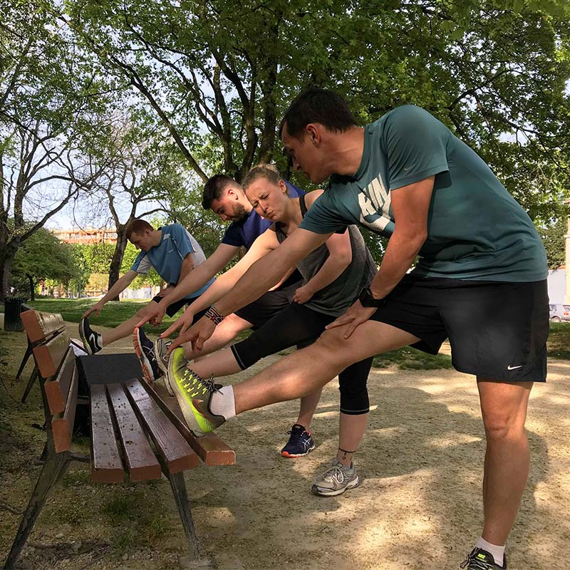 Séance d'étirements sur un banc en groupe dans un parc