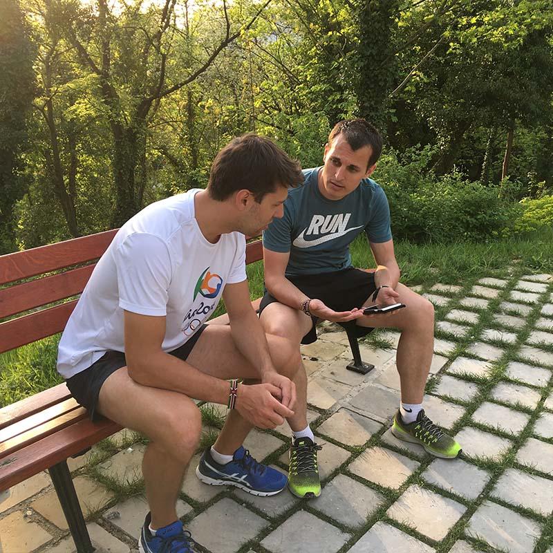 Benjamin André discute avec un élève de son suivi sur un banc dans un parc