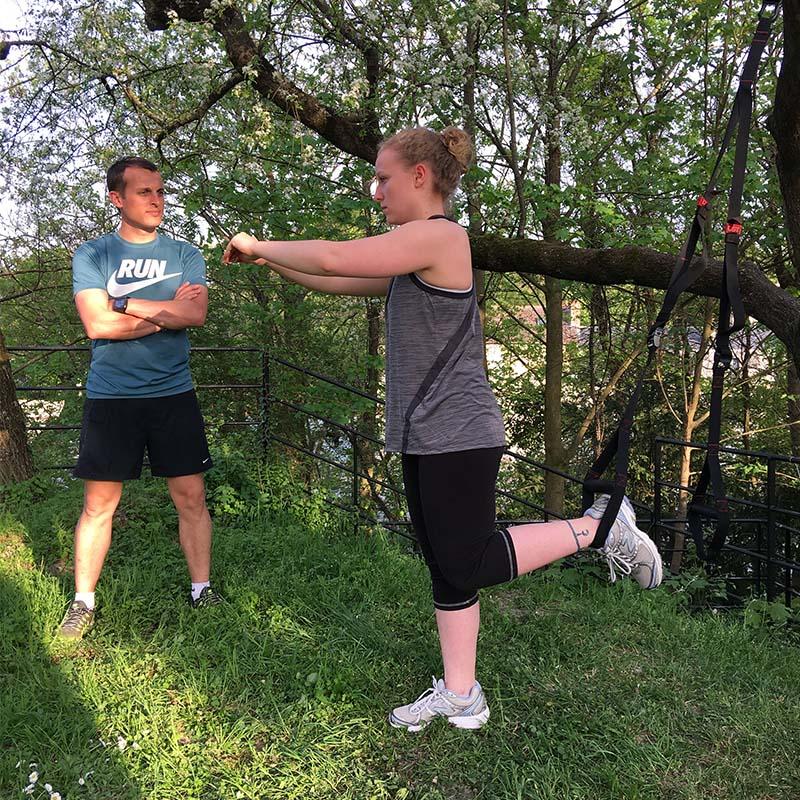 Exercices de renforcement musculaire au TRX dans un parc